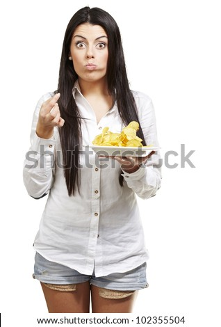 young woman eating potato chips against a white background