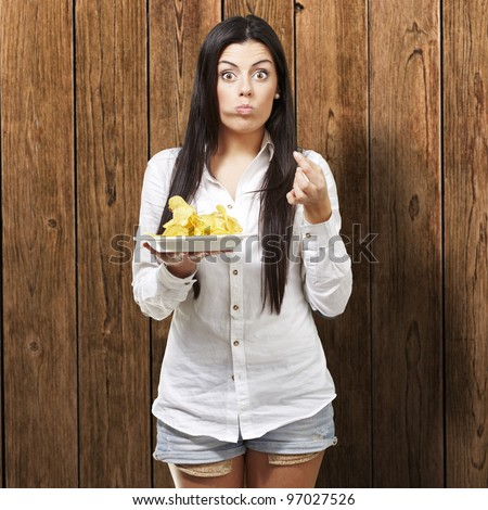 young woman eating potato chips against a wooden background