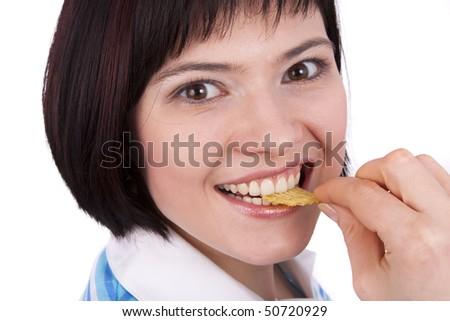 Young woman eating potato chips. Lovely girl eating potato chips. Eating potato chips / crisps. Cute woman having a junk food snack while looking up at camera