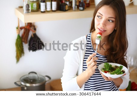 Young woman eating salad and holding a mixed salad . - stock photo