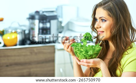 young woman eating salad sitting in kitchen . caucasian female model  for green vegetarian diet concept. - stock photo