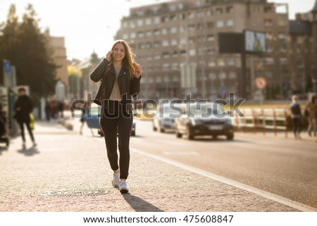 Young woman eating sandwich and calling phone while walking street on sunny day