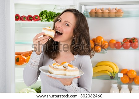 Young Woman Eating Slice Of Cake Near The Open Refrigerator - stock photo