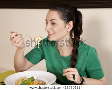 Young woman eating spaghetti - stock photo