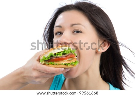 Young woman eating tasty fast food unhealthy burger in hand getting ready to eat isolated on a white background. - stock photo
