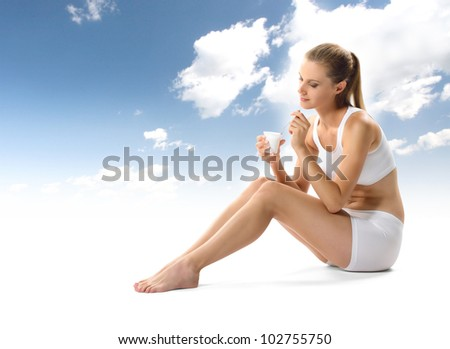 Young woman eating yogurt as breakfast or snack - stock photo