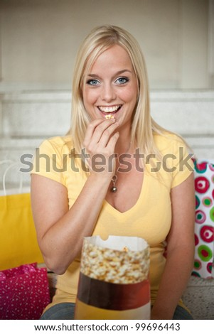 young woman eats popcorn out of a bag/young woman eats popcorn/woman with popcorn