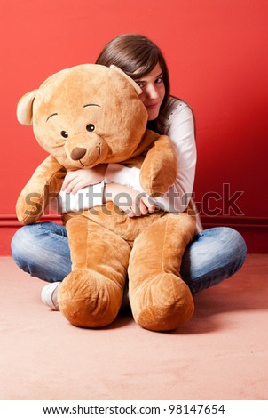 Young woman embracing teddy bear sitting on floor - stock photo