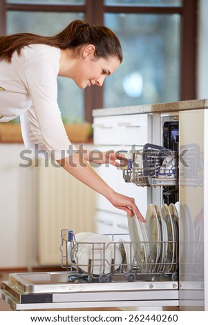 Young woman empty out the full dishwasher
