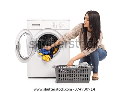 Young woman emptying a washing machine isolated on white background - stock photo