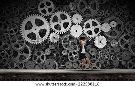 Young woman engineer holding mechanism of cogwheels above head - stock photo