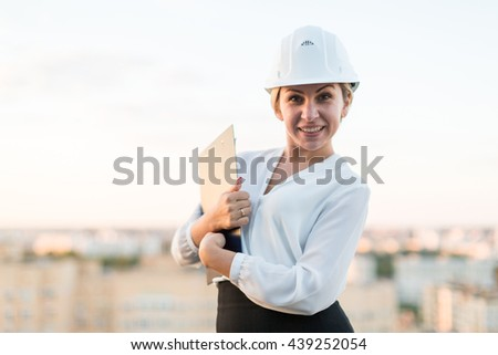 Young woman engineer in a helmet with a folder is a folder on the background of the city - stock photo