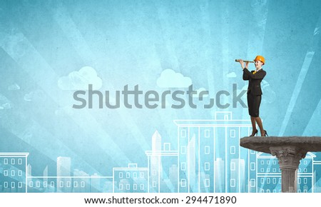 Young woman engineer on top looking in spyglass - stock photo