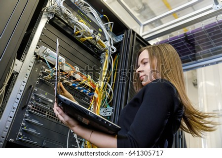 Young woman engineer with a laptop talking on the phone at the network equipment between the server racks in the data center