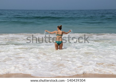Young woman enjoy beautiful huge waves of turquoise sea