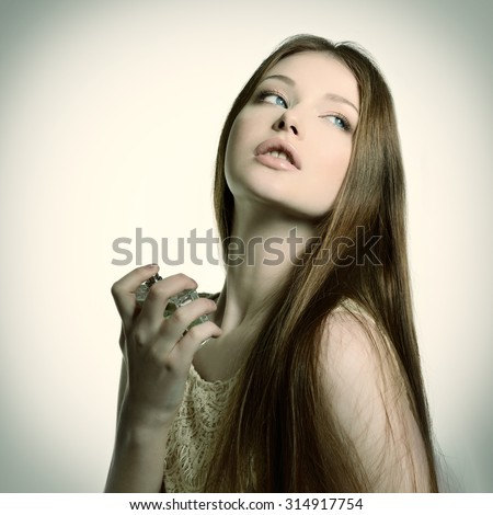 Young woman enjoy the fragrance of perfume, image toned. - stock photo