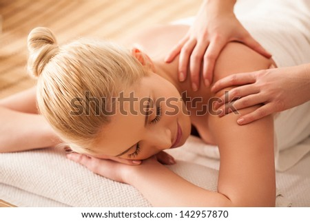Young woman enjoying a back massage at a spa centre. - stock photo