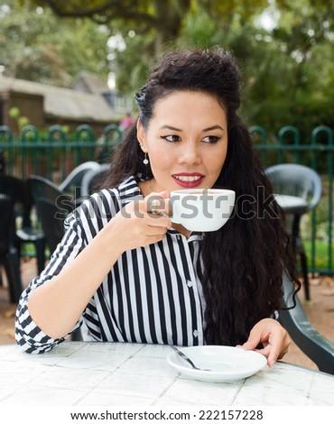 young woman enjoying a coffee - stock photo