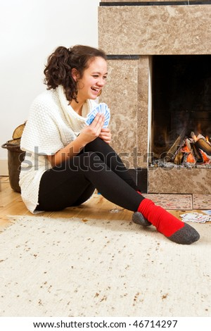 Young woman enjoying a cosy game of cards by the warmth of a fireplace - stock photo