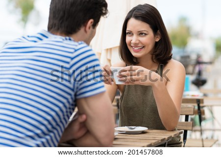 Young woman enjoying a cup of coffee outdoors at a street cafe as she sits chatting to her boyfriend or husband in the summer sun - stock photo