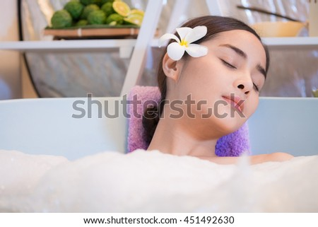 Young woman enjoying a massage, spa and beauty. Water treatment.Bathing woman relaxing in bath smiling relaxing with eyes closed. Multicultural Asian   - stock photo