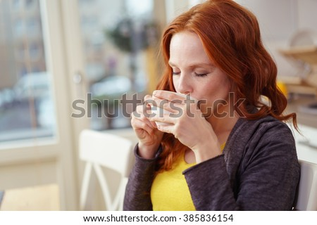 Young woman enjoying a morning cup of coffee or tea at home closing her eyes with pleasure as she savors the taste - stock photo