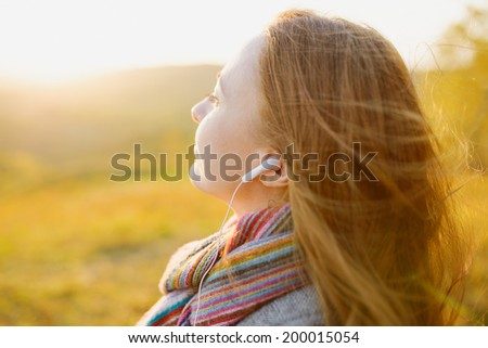 Young woman enjoying a music in the fall season. Autumn outdoor portrait. - stock photo