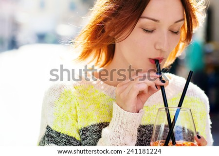 Young woman enjoying a orange drink - spritz - on a sunny day.