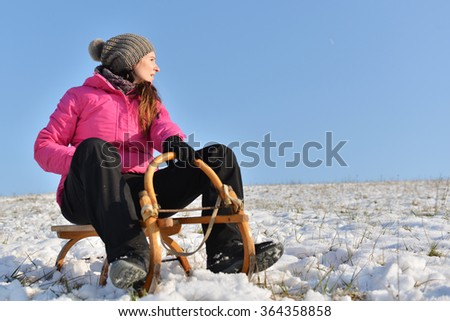 Young woman enjoying a sledge ride in a beautiful snowy winter park