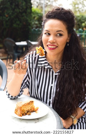 young woman enjoying a slice of cake.