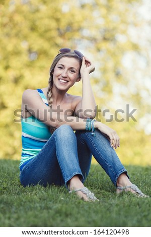 Young woman enjoying a summer day sitting in her jeans on the green grass in the garden raising her sunglasses to the top of her head and smiling at the camera - stock photo