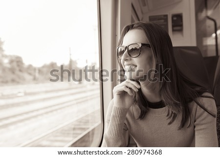 Young woman enjoying a train ride.  - stock photo