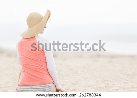 young woman enjoying beach vacation and protecting skin against harmful UV rays with rashguard - stock photo