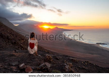 Young woman enjoying beautiful sunset sitting on the mountain with great view on Cofete coastline on Fuerteventura island - stock photo