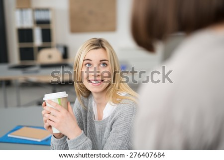 Young woman enjoying coffee in the office cradling a large takeaway mug in her hands as she has a discussion with a female co-worker - stock photo
