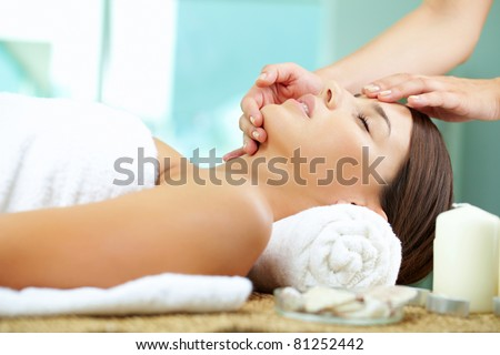 Young woman enjoying facial at spa salon - stock photo