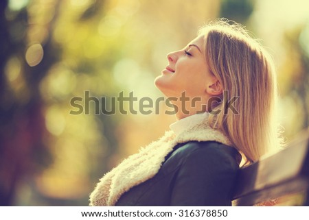 Young woman enjoying fresh air in autumn, intentionally toned. - stock photo
