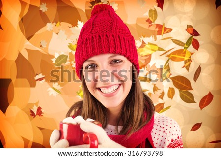 Young woman enjoying her hot coffee in the winter against autumnal leaf pattern