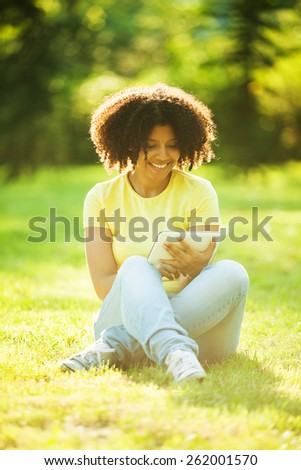 Young woman enjoying her time in park with tablet computer - stock photo