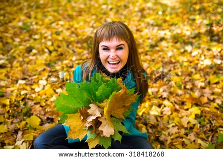 Young woman enjoying in autumn park playing with leaves, snail on the nose - stock photo