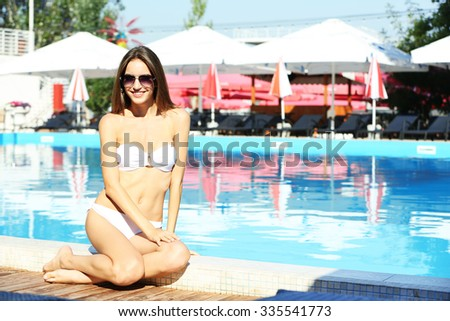 Young woman enjoying in swimming pool at summertime