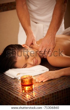 Young woman enjoying massage with eyes closed in wellness environment.? - stock photo