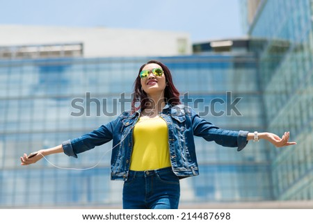 Young woman enjoying music in her earphones while standing outdoors - stock photo
