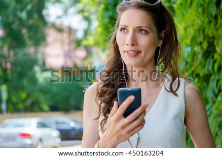 Young woman enjoying music in park on warm summer day - stock photo