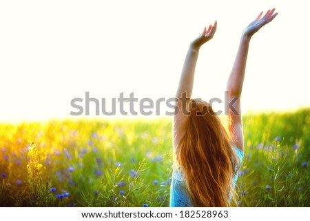 Young woman enjoying nature and sunlight in canola field