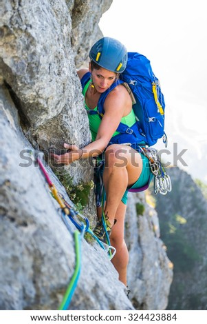 Young woman enjoying rock climbing - stock photo