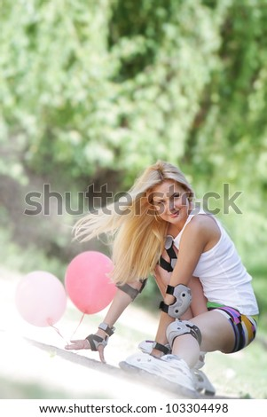 young woman enjoying rollerblading / roller skating on natural background - stock photo