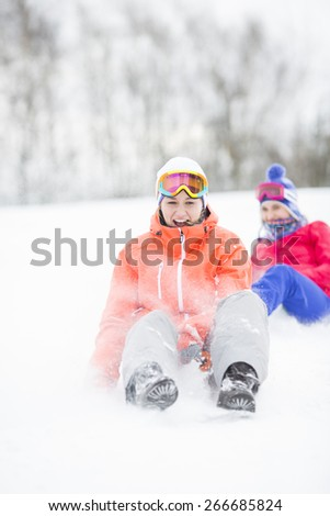 Young woman enjoying sled ride in snow with friend in background - stock photo