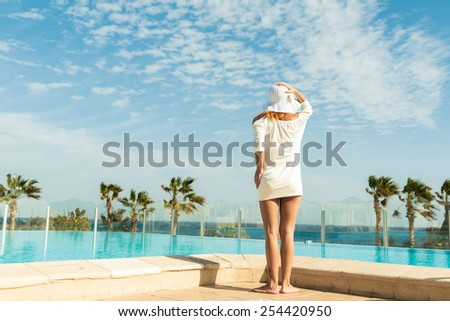 Young woman enjoying sun by pool at tourist resort - stock photo