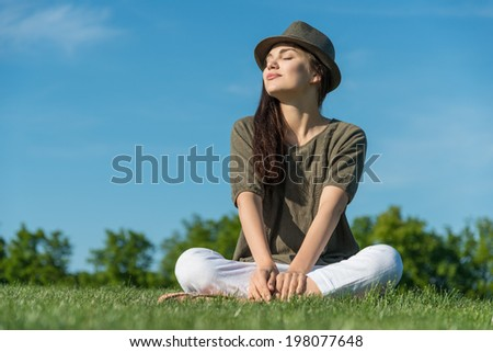 Young woman enjoying sun in the park - stock photo